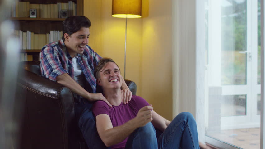 4K Affectionate gay male couple relaxing at home & chatting. Shot on RED  Epic.