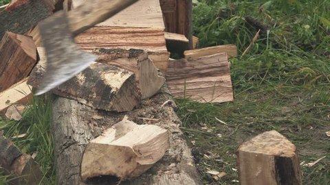 Man cutting firewood logs with axe in home backyard