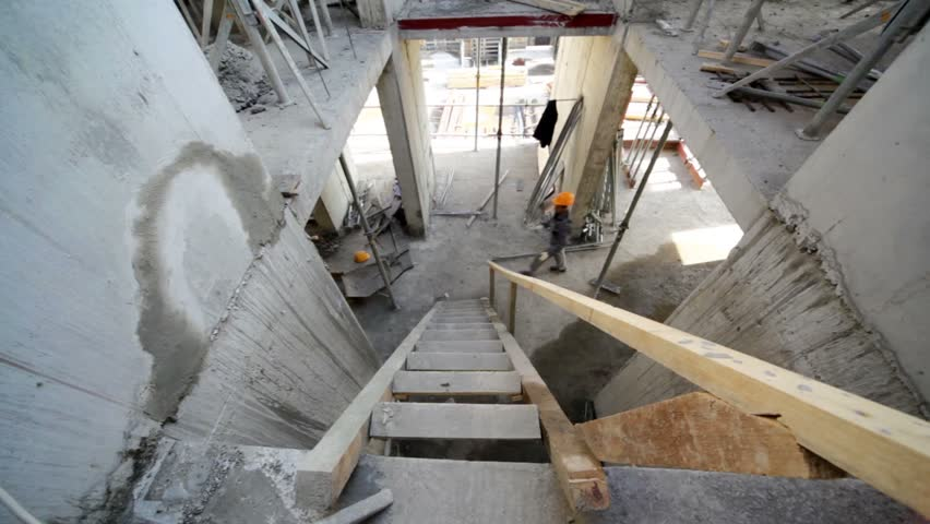 Builder walk up by wooden stairs on next floor, view from above