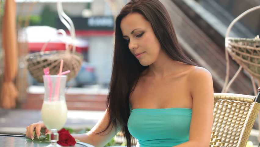dreaming lady with a rose in hand, sitting in a restaurant - HD stock footage clip
