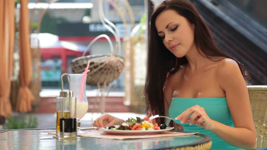 young woman having dinner at a restaurant. Her choice Greek salad and a cocktail - HD stock footage clip