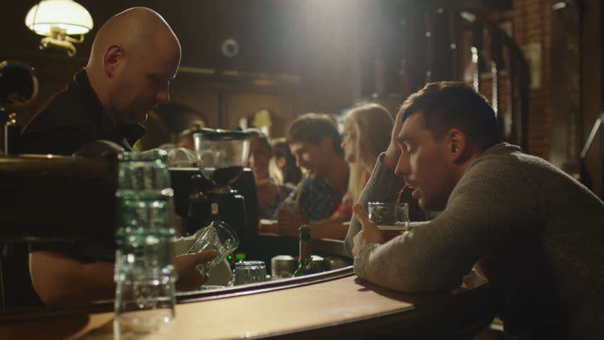Sad lonely man is chatting with bartender and drinking beer in a bar. Shot on RED Cinema Camera in 4K (UHD). #13389557