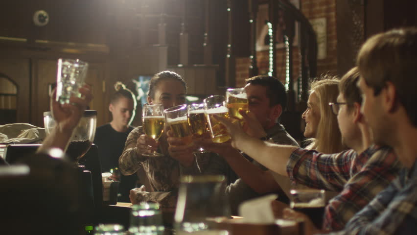 Friends do toasts, drink beer and cocktails while having a good time together at a bar. Shot on RED Cinema Camera in 4K (UHD). | Shutterstock HD Video #13390304