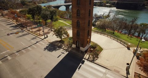 The camera moves forward and gains altitude over the bell tower that prominently stands at Cesar Chavez and Colorado streets.  Lady Bird Lake is revealed with traffic crossing Congress Avenue bridge.
