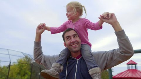 Father spins his little girl on his shoulders