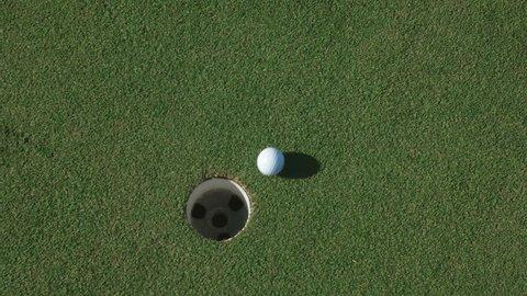 golf ball enter hole at golfing course