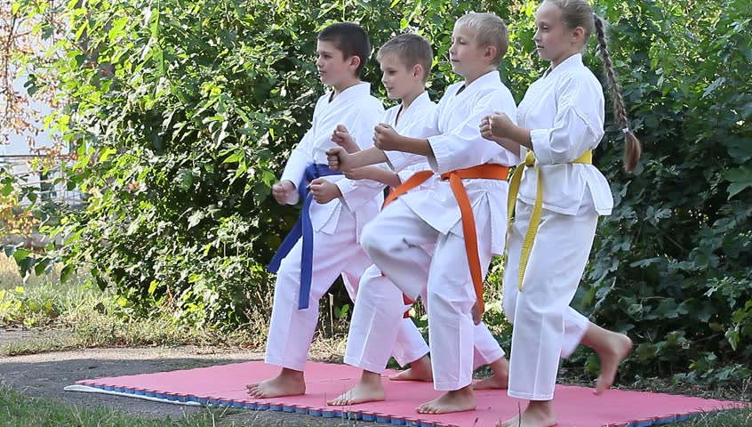 Boy and girl are doing karate techniques outdoors