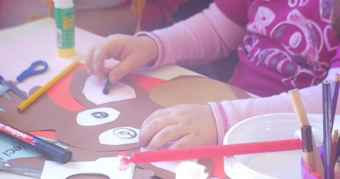 Little Girl in Pink Blouse is Painting an Eyes Pupils of a Paper Deer, Cow, Applique, Kid is Painting with Black Marker, Educator, Woman's Hand, Woman Helps the Kid, Shows Where to Paint, Pencils,