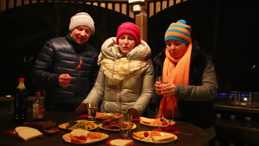 Two women and man stand at table, eat grilled meat and drink wine at winter night | Shutterstock HD Video #13504094