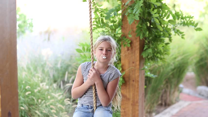 Pre-teen girl on a swing blowing bubbles with bubblegum