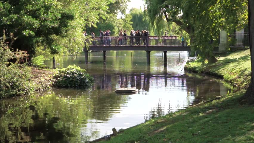 A beautiful lake in Regent's Park in central London surrounded by trees. People stand and walk on a bridge enjoying the peaceful scene