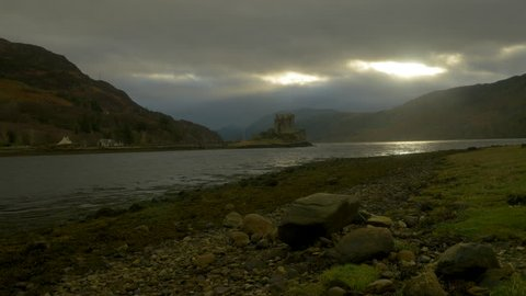 Eilean Donan Castle revealing shot with moody sky and rain. Slider shot.