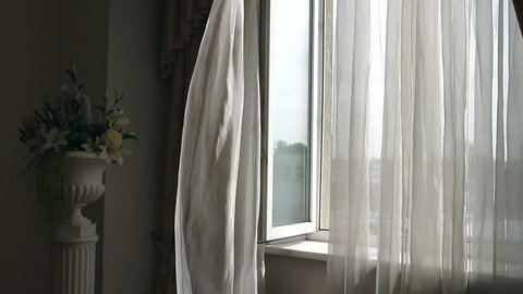 Curtain fluttering in the wind at the window. Wind at the window. A breath of wind. Open window. Curtain fluttering. The inside of the house. Interior of the house. Inspiration.