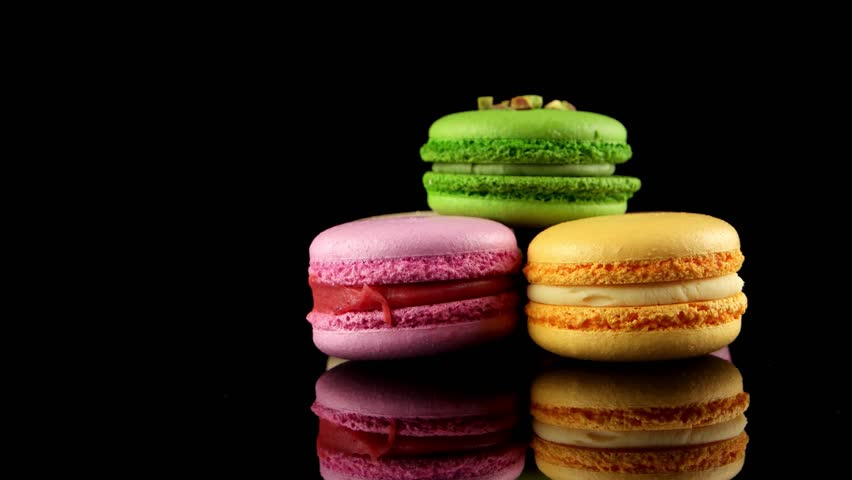 Traditional French colorful macarons on the black background