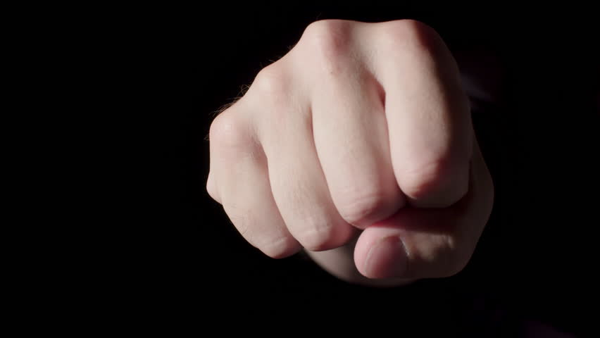 Man's fist punches out of a dark background towards camera and stops.  Big close up, repeated three times quickly, then once more.  Four punches total, last one in slow motion, recorded at 60fps.