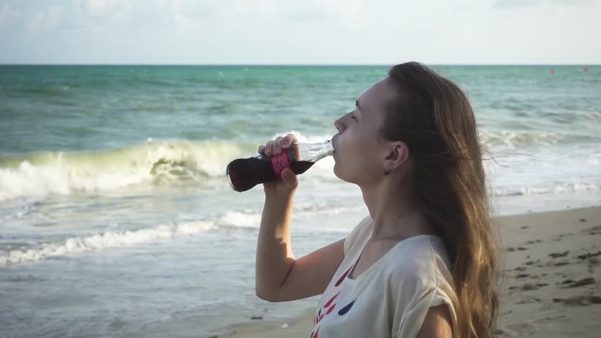 Girl drinking a refreshing drink from glass bottle while standing on the beach against stormy sea. Slow motion