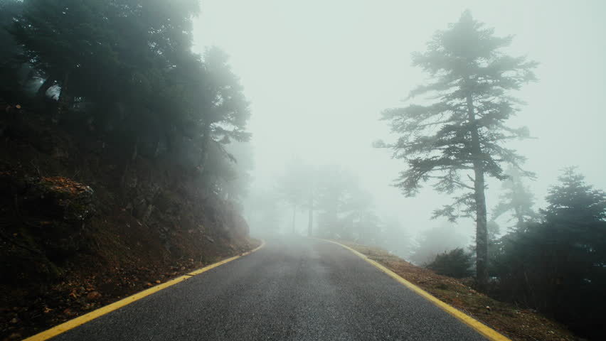 4K UHD Pov drive mountain road winter fog overcast.Stabilized gimbal pov wide angle driving plate shot of a car driving through a Greek mountain forest road at winter in fog and mist.