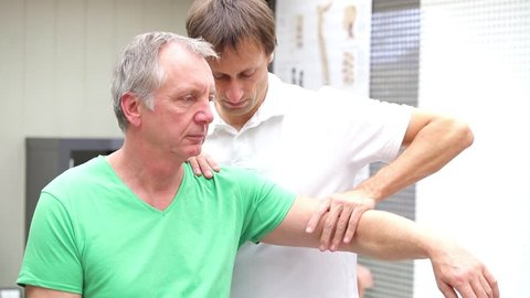 Medicine or physiotherapist performing jobe test at a patient with shoulder pain. This is a test for detection of impingement syndrome,