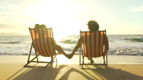 Relaxing Couple on Tropical Resort Luxury Vacation. Beach Chairs in the Sunset. Slow Motion.