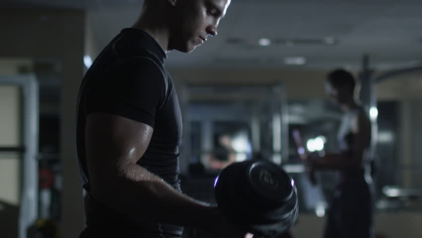 Handsome fit sporty man does dumbell curl exercises in dark gym. Shot in 4K (UHD).