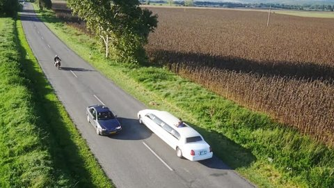 White limousine passing by. Top view recorded by drone from the sky.