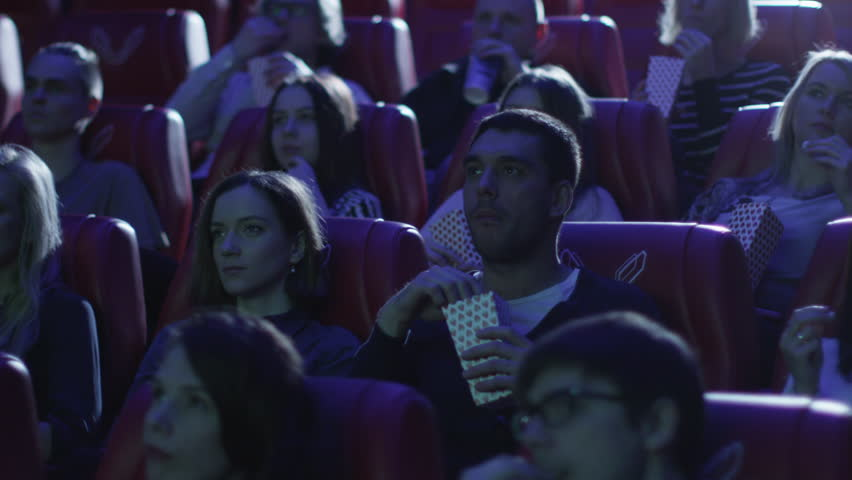 Group of people are scared while watching a horror film screening in a movie cinema theater. Shot on RED Cinema Camera in 4K (UHD).