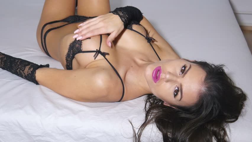 Sexy black lingerie fashion model woman on bed being sensual