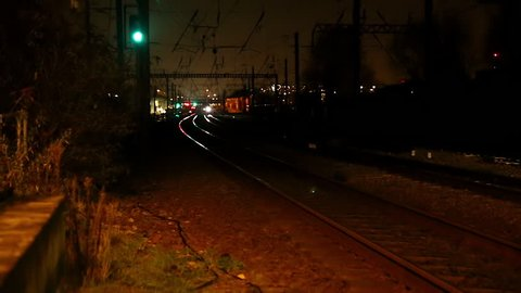 overground train passing tracks towards camera at night on station platform in the evening in London