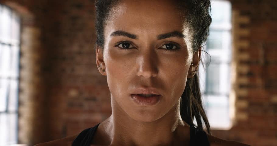 Beautiful Kickboxing woman training punching bag in fitness studio fierce strength fit body