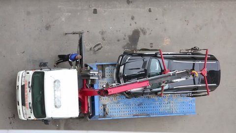 Top view of modern tow truck loading broken black car