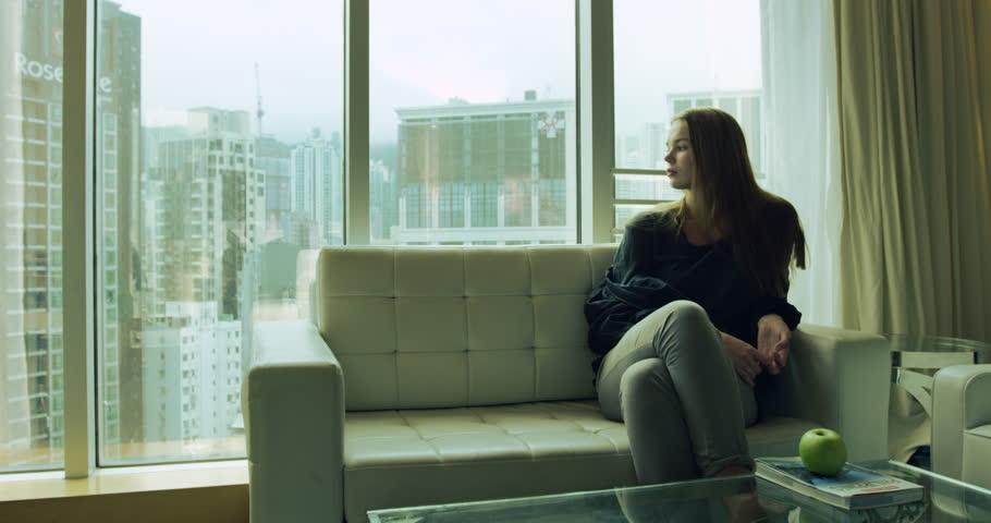 Hong Kong, Republic of China - Young woman sitting in sofa top floor hotel Hongkong skyline looking out window. Sky line urban city unfolds below. Hong Kong, Republic of China February 2016 | Shutterstock HD Video #13781054