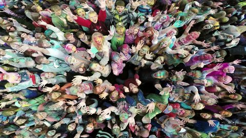 Russia, Chelyabinsk, 13 June 2015: Aerial flight above dancing crowd on Holi Festival Of Colors. Crowd of people colored powder and having fun in arena
