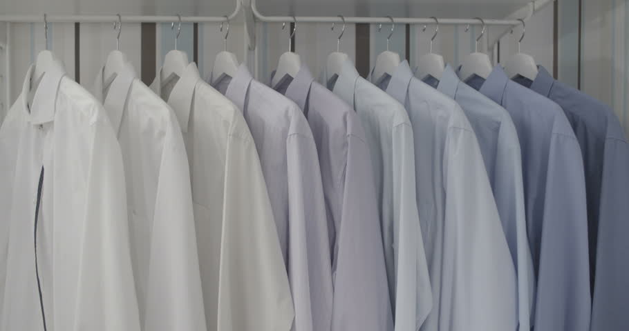 Clean ironed men's shirts set in colors hanging on hangers in the wardrobe flat color