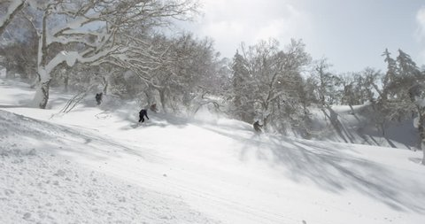 Hokkaido, Japan -  A group of skiers skiing down the side of a volcano. Kamifurano volcano hiking powder climbing skins bindings skis boots sun. Hokkaido, Japan February 2016.
