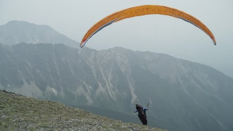WS Man paragliding in Rocky Mountains / USA