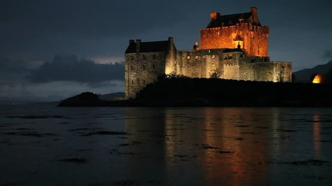 A beautiful Scottish castle is lit up at night as rain falls on a lake in the foreground.
