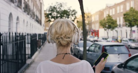 Happy Beautiful blonde listening to music on smart phone walking in the city