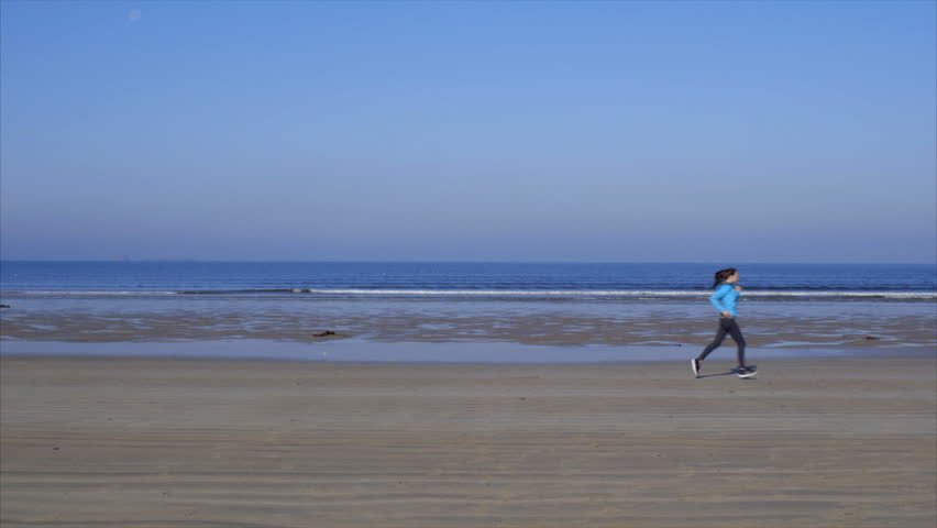 Lockdown shot of idyllic beach against clear blue sky. Side view of fit woman jogging on shore. Female is in sportswear. Full length of determined woman exercising, waves in background. | Shutterstock HD Video #13837484