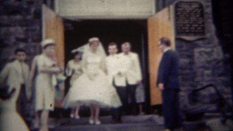 BUFFALO, NEW YORK 1956: Newlywed couple leaving church steps rice tossed.
