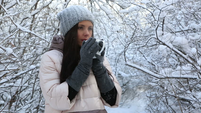 Beautiful happy girl warms up with hot tea. Snow covered trees in winter park. | Shutterstock HD Video #13880324