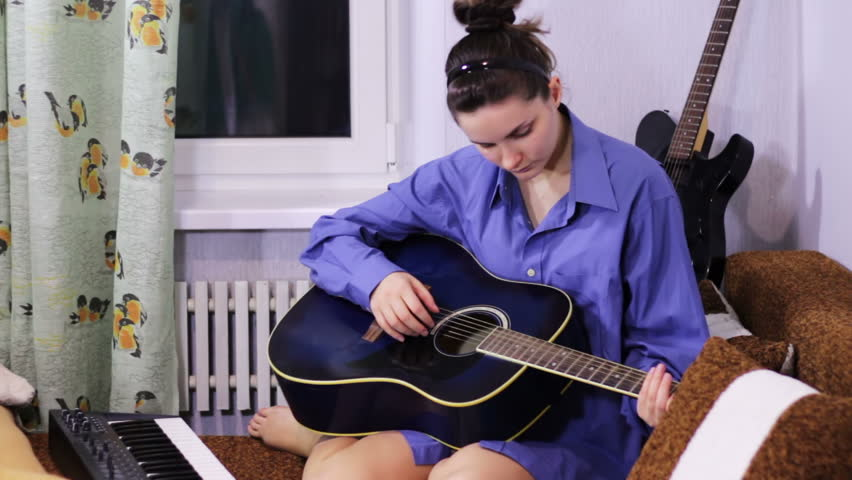 Young beautiful girl learning to play the guitar at home. #13894484