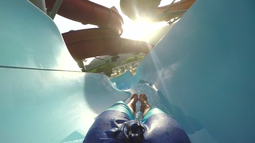 FPV FIRST PERSON VIEW POV: Man in boardshorts swimsuit sliding down the fun tobogan water slide in sunny summer | Shutterstock HD Video #13913984