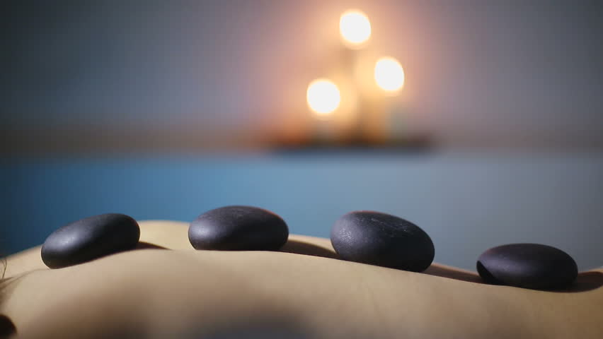 Woman getting hot stone massage in spa salon | Shutterstock HD Video #13942244