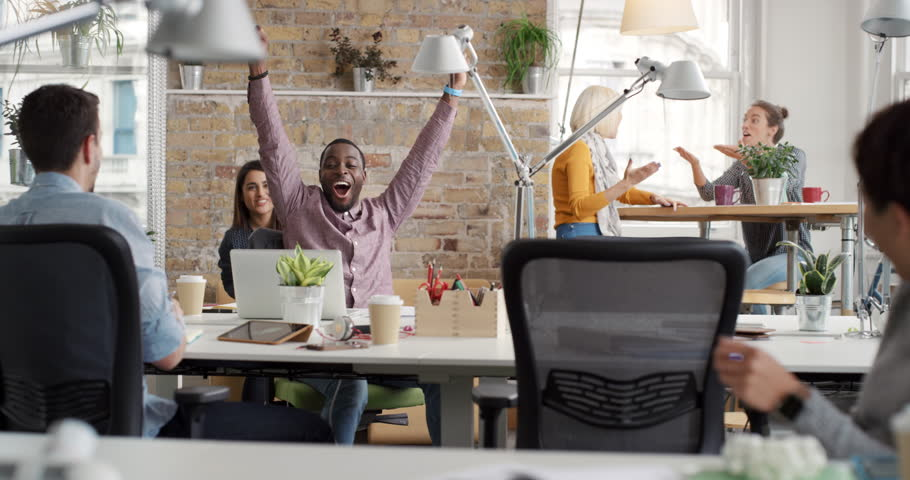 Businessman with arms raised celebrating success watching sport victory on laptop diverse people group clapping expressing excitement in office | Shutterstock HD Video #13947464