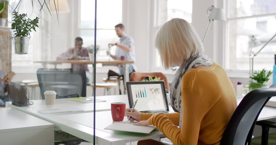Young business woman working at shared desk in trendy hipster start up office using big data on laptop computer | Shutterstock HD Video #13949624