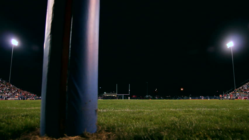 Dolly of a crowded football field at night.