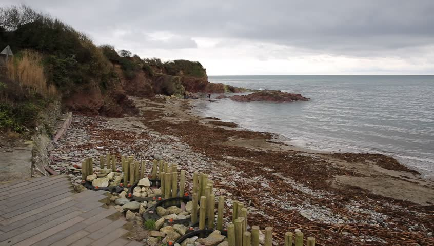 Talland Bay beach with pebbles and seaweed Cornwall between Looe and Polperro England UK quiet and out of season in winter smooth professional pan