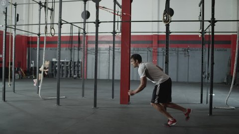 Tracking shot following a man sprinting in a gym with a woman in the back ground - fitness / crossfit - exercise / / workout / runner / running