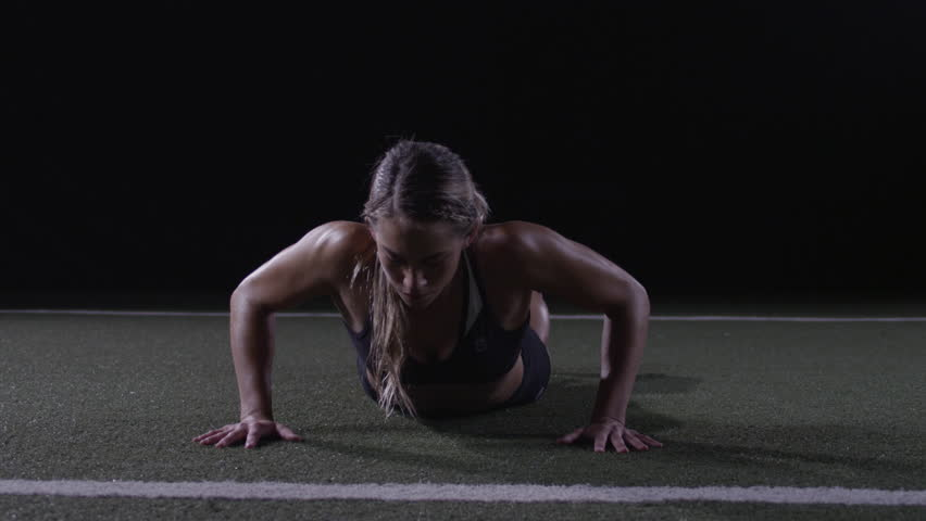 A woman does a burpee on artificial turf facing the camera in slow motion - fitness / crossfit / exercise / workout