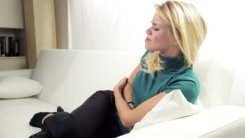 Beautiful blond woman feeling strong belly stomach ache at home sitting on sofa